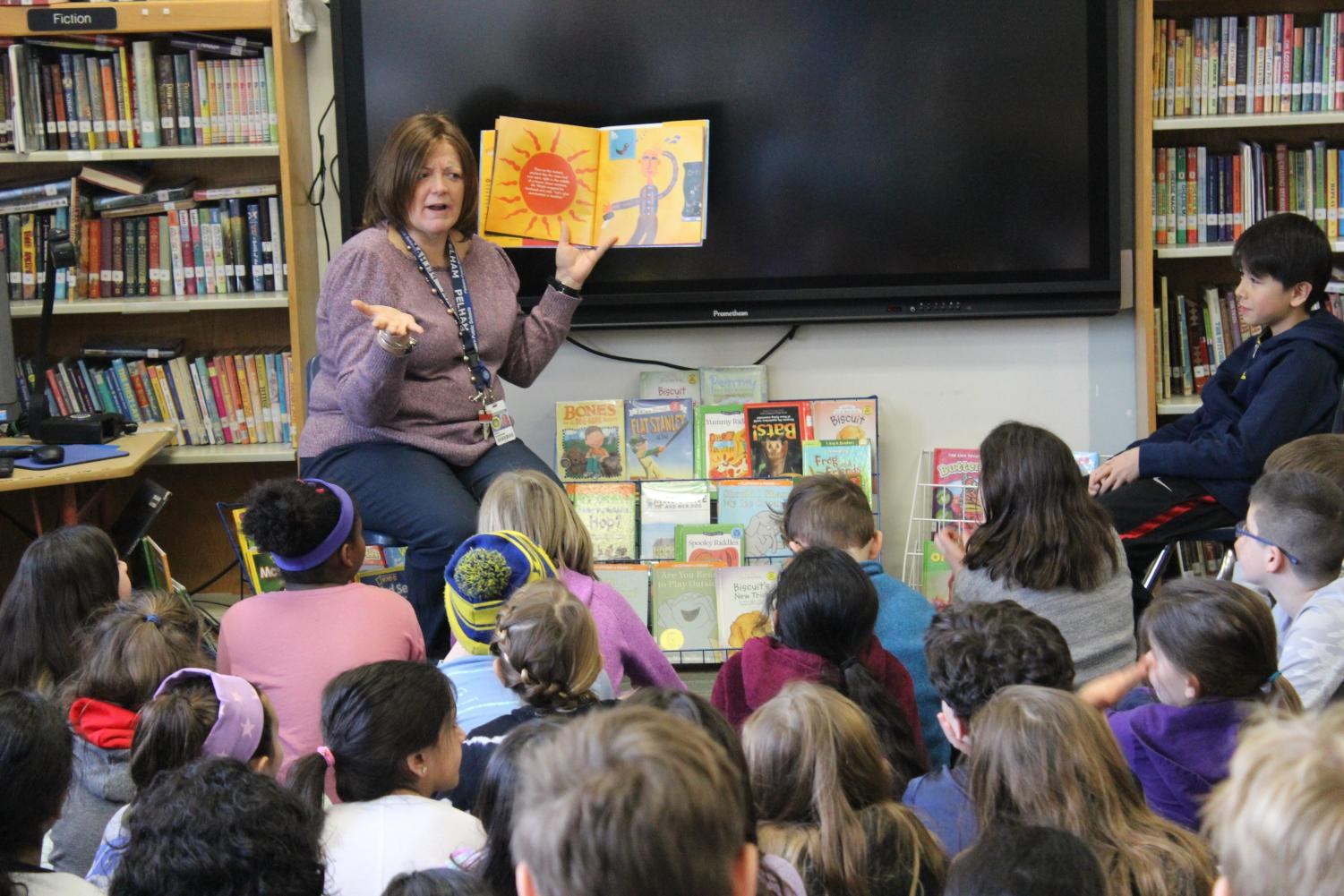 Dr. Maria Thompson, director of humanities, reads to students at Siwanoy School.